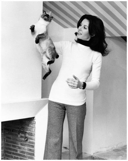 Gabriella Farinon pickingup a cat, Elliott Erwitt, 1970's