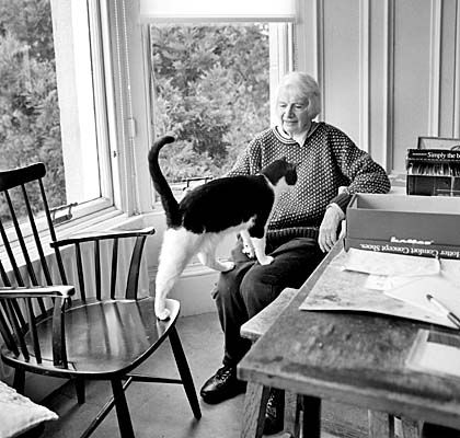 Elizabeth Blackadder sitting at a table in her studio with a cat (Photo by Anne Purkiss)