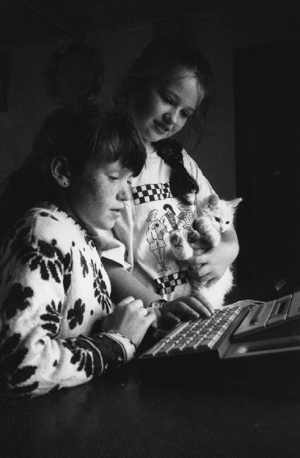 Christina Rodgers and Donna with kitten, in front of their video game, Martine Franck